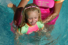 Kid swimming. A beautiful blond caucasian white little girl with happy exciting expression in her pretty face wearing a colorful swimsuit having great fun by Royalty Free Stock Photos
