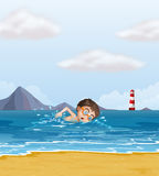 A kid swimming at the beach with a lighthouse Royalty Free Stock Photos
