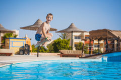 Kid swimming and jumping in pool. summertime Royalty Free Stock Photos