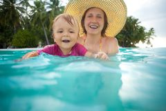 Kid swimming with mothers help Royalty Free Stock Image