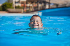 Kid swimming and playing in pool. summertime Royalty Free Stock Photography
