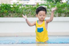 Kid in swimming pool. Little boy splashing in swimming pool royalty free stock image