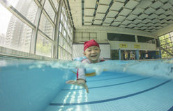 Kid swimming in pool with smile. Kid swimming in pool with lifebelt and swimming hat Royalty Free Stock Photography