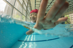Kid swimming in pool with smile. Kid swimming in pool with lifebelt and swimming hat Stock Photos