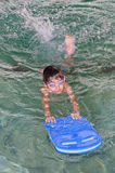 Kid swimming surf board Stock Photos