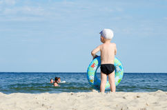 Kid in swimming trunks and a cap with a swimming circle stands on the shore of the sea back Royalty Free Stock Photos