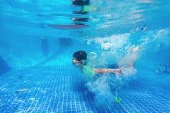 Kid swimming underwater in pool