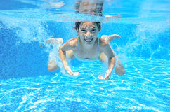 Kid swims in pool underwater Stock Photo