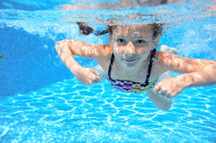 Kid swims in pool underwater, girl swimming Stock Photo