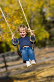 Kid on swing. Kid swinging on swing with autumn leaves and wood fence out of focus in background Royalty Free Stock Photo