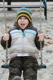 Kid on a swing. 5 years old child on a swing in a playground Stock Image