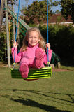 Kid swinging. A full body of a beautiful blond caucasian white girl child with happy laughing expression in the pretty face dressed in pink clothes sitting on a Stock Photos