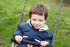 Kid swinging happy in the park on a cold day Royalty Free Stock Image