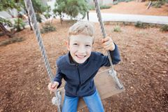 Kid at swings. Wide angle portrait of cheerful adorable little boy enjoying his childhood at swings in the park Royalty Free Stock Images