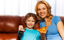 Kid switching TV and mother with pizza Stock Photos