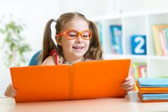 Kid at the table with books stock image