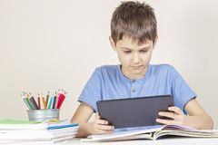 Kid with tablet computer sitting at table with books notebooks stock image