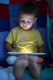 Kid with tablet in the dark Stock Photography