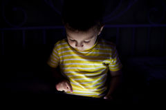 Kid with tablet in the dark Royalty Free Stock Image