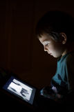 Kid with tablet in the dark. Laying in bed and reading royalty free stock images