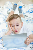 Kid with tablet pc. Adorable kid with tablet pc lying on the bed Royalty Free Stock Photos