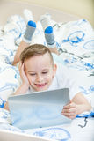 Kid with tablet pc. Adorable kid with tablet pc lying on the bed Stock Photo