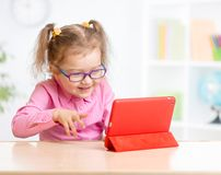 Kid with tablet PC in glasses learning with Stock Photos