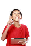 Kid with tablet pointing. Portrait of asian kid with tablet pointing at white background Royalty Free Stock Images