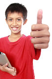 Kid with tablet showing thumb up. Portrait of asian kid with tablet showing thumb up to camera Royalty Free Stock Photography