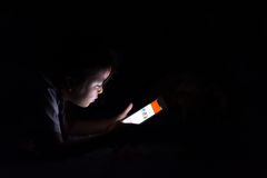 Kid with tablet sitting on bed and watching cartoons at night. royalty free stock photos