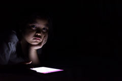 Kid with tablet sitting on bed and watching cartoons at night. stock image