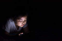 Kid with tablet sitting on bed and watching cartoons at night. royalty free stock image