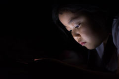 Kid with tablet sitting on bed and watching cartoons at night. stock photo