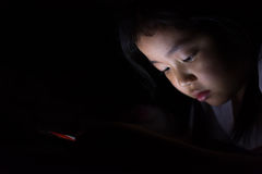 Kid with tablet sitting on bed and watching cartoons at night. Stock Photos