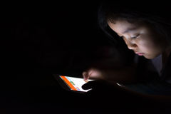 Kid with tablet sitting on bed and watching cartoons at night. Stock Images