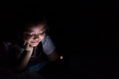 Kid with tablet sitting on bed and watching cartoons at night. royalty free stock images