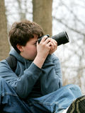 Kid taking photos. Young teen boy taking photographs with his camera in the woods Stock Photography