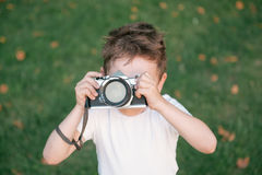 Kid taking a picture using film camera. Little boy taking a picture using vintage film camera on green grass and fallen leaves background in autumn Royalty Free Stock Photos