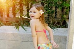 Kid taking shower, drops of water fall on little girl in swimsuit shower on sunny day outside. Sweet kid taking shower, portrait of water drops fall on little royalty free stock image
