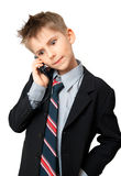 Kid talking on a cell phone. Cute  Boy in Suit talking on a cell phone over a white background Royalty Free Stock Photography