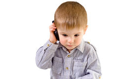 Kid talking on a mobile phone. Beautiful small kid talking on a mobile phone Royalty Free Stock Photos