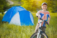 Kid with a tent on a camomile meadow Stock Photos
