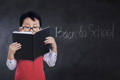 Kid with text Back to School reads book. Little boy standing in the classroom and reads a book with text Back to School on the chalkboard Stock Photos