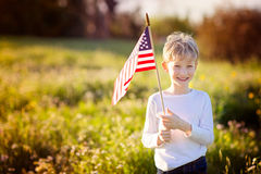 Kid at 4th of july. Happy proud caucasian boy holding american flag celebrating 4th of july outdoors Royalty Free Stock Photo
