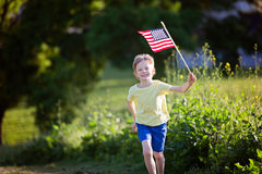Kid at 4th of july. Happy smiling little boy running with american flag, celebrating 4th of july stock photos
