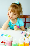 Kid thinking and painting Royalty Free Stock Image