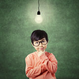 Kid in thinking poses while looking at light bulb Royalty Free Stock Images