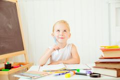 Kid thinking wile doing her homework. royalty free stock photography