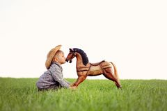 A small child, a boy is kissing a rocking horse on a meadow. Happy childhood in the countryside, the child looks after his pet royalty free stock image