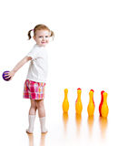 Kid throwing ball to knock down toy pins Royalty Free Stock Images